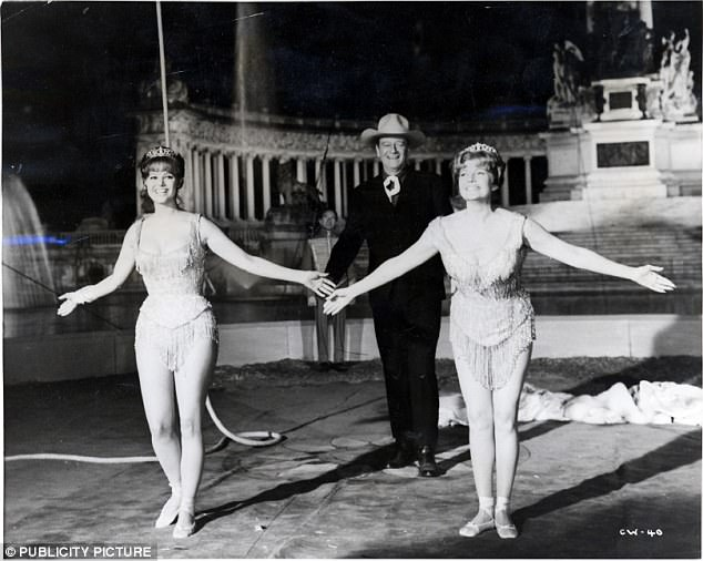 John Wayne as Matt Masters, Claudia Cardinale as Toni Alfredo (left) and Rita Hayworth as Lili Alfredo (right) in the 1964 film The Magnificent Showman